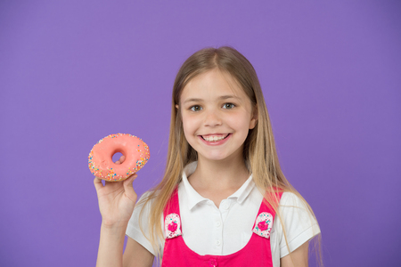 Do you want bite. Girl smiling face holds pink donut in hand, violet background. Kid smiling girl ready to bite donut. Snack concept. Child can not wait to eat sweet donut, copy space