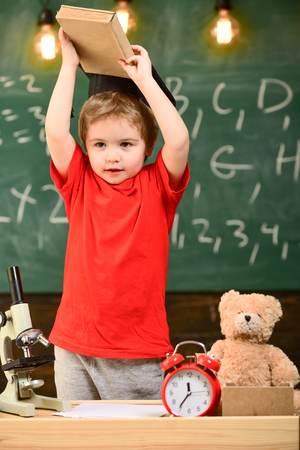 Child, pupil on cheerful face near microscope. Wunderkind concept. First former interested in studying, education. Kid boy in graduate cap holds book in classroom, chalkboard on background Stock Photo