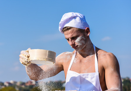 Man muscular baker or cook sifts flour through sieve. Pizzaiolo concept. Hands of chef cook covered with sticky dough and flour. Baker at working with flour and sieve, kneading dough