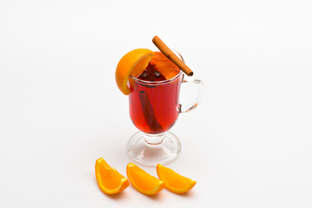 Mulled wine near slices of orange. Cocktail and bar concept. Glass with mulled wine or hot cider near orange fruit and slices on white background. Drink or beverage with orange and cinnamon
