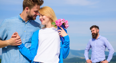 Ex partner watching girl starts happy love relations. New love. Couple in love dating outdoor sunny day, sky background. Ex husband jealous on background. Couple with flowers bouquet romantic date
