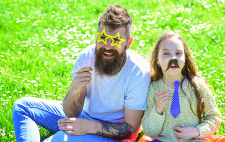 Best friends concept. Dad and daughter sits on grass at grassplot, green background. Child and father posing with eyeglases, mustache and tie photo booth attributes. Family spend leisure outdoors
