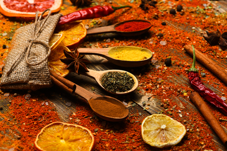 Spices concept. Spices scattered all over wooden surface. Spoons filled with cinnamon, grinded red pepper and curcuma powder and kitchen herbs scattered on table. Spoons with spices on wooden texture