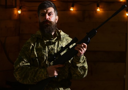 Man with beard wears camouflage clothing in wooden interior background. Gamekeeper concept. Hunter, brutal hipster with gun in his hand ready for hunting. Macho on strict face at gamekeepers house Stock fotó