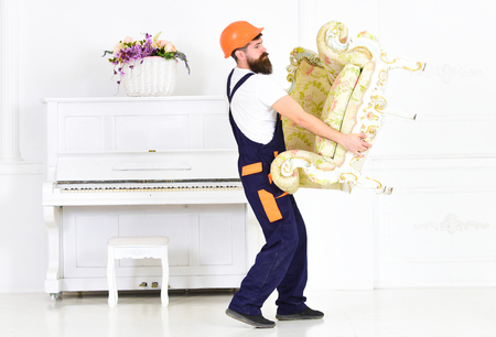 Relocating concept. Man with beard, worker in overalls and helmet lifts up armchair, white background. Courier delivers furniture in case of move out, relocation. Loader carries armchair
