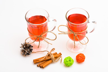 Hot drinks concept. Glasses with mulled wine or cider tied with twine string on white background. Mulled wine or hot beverage in glasses and cinnamon sticks. Traditional mulled wine with spices