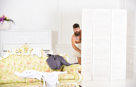 Hipster naked on shocked face unexpectedly detected in bedroom. Exposing lovers concept. Man with beard and mustache hiding behind folding screen. Man, lover in white interior caught naked Фото со стока
