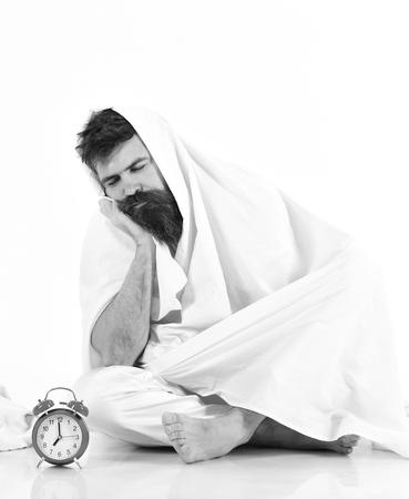 El hombre con rostro tranquilo y aburrido se sienta debajo de una manta cerca del despertador. El hombre quiere quedarse en la cama, fondo blanco.