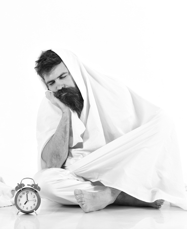 Man with calm, bored face sits under blanket near alarm clock. Man wants to stay in bed, white background. Stock Photo - 103311424