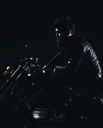 Bikers leisure concept. Macho, brutal biker in leather jacket riding motorcycle at night time, copy space. Man with beard, biker in leather jacket sitting on motor bike in darkness, black background 免版税图像