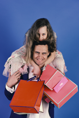 Girl and man with happy smiling faces hold shopping bags