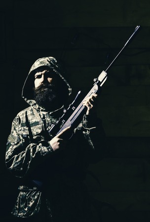 Hunter, brutal with gun prepare rifle for hunting. Huntsman concept. Macho on strict face at gamekeepers house. Man with beard wears camouflage hooded clothing, wooden interior background.