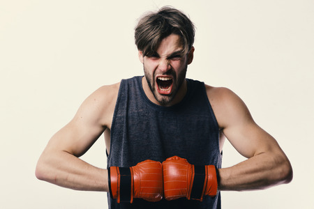 Man with bristle and furious face wears boxing gloves. Boxer makes hits and punches as training. Sports and competition