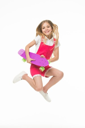 Happy child jump with penny board isolated on white. Little kid smile with skateboard. Fun in motion. Sense of freedom. Childhood development. Carefree skater girl. Active hobby and sport activity