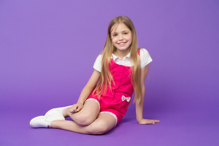 Happy girl relax on violet background. Beauty and fashion look. Little child with smile on cute face, beauty. Fashion kid smiling with long blond hair. So young and so stylish. Cute and fashionable