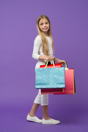 Happy kid carry shopping bags on violet background. Little shopaholic smile with paper bags. Girl shopper smiling with paperbags. Childhood. Holidays preparation and celebration. Shopping and sale