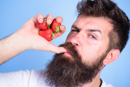 Fresh juice concept. Man strict face enjoy fresh drink strawberry juice. Man drinks strawberry juice suck thumb as drink straw blue background. Hipster bearded holds strawberries fist as juice bottle