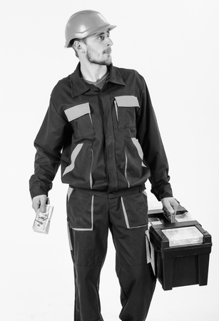 Man with toolbox walks, holds money. Builder holds money, repairman holds cash, banknotes in hand.