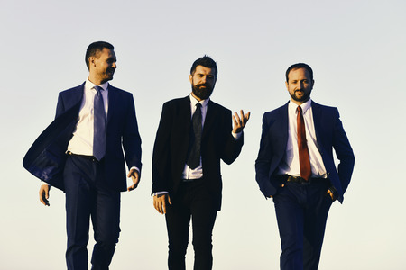 Managers go ahead and talk. Leaders with beard and smiling faces discuss project.
