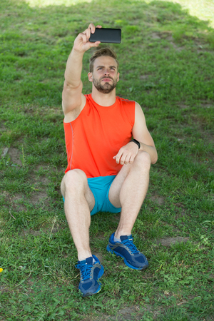 New technology and modern life. Macho sit on green grass with smartphone. Summer activity and sport. Man make selfie with mobile phone on fresh air. Sportsman relax after training. Sport and fitness Stockfoto