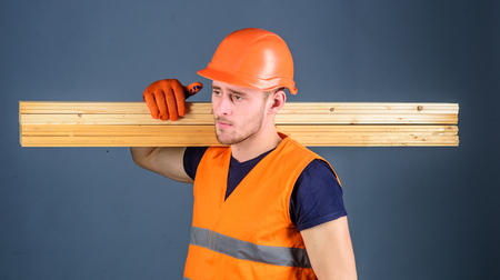 Carpenter, woodworker, strong builder on serious face carries wooden beam on shoulder. Man in helmet, hard hat and protective gloves holds wooden beam, grey background. Wooden materials concept