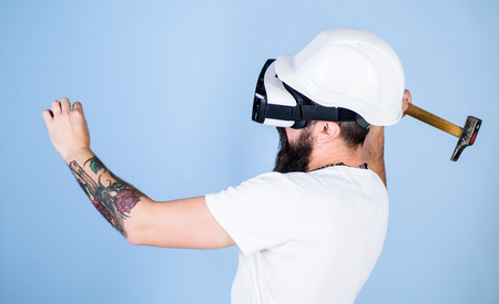Builder and renovation concept. Hipster busy with renovation in virtual reality. Guy with HMD hammering virtual nail into VR surface. Man with beard in VR glasses holds hammer, light blue background. Stock Photo
