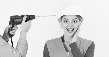 Drill makes hole in female head. Stress resistance concept. Lady happy and carefree. Male hands with drill drills head of woman, white background. Woman with smiling face in helmet, hard hat.