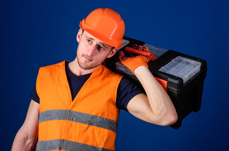 Repair and renovation concept. Worker, repairer, repairman, strong builder on thoughtful face carries toolbox on shoulder, ready to work. Man in helmet, hard hat holds toolbox, blue background. Archivio Fotografico