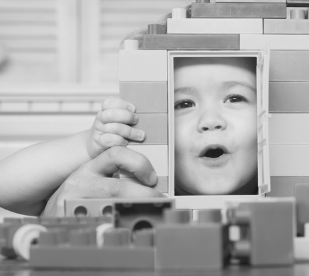 Family and childhood concept. Kid looking through door of toy house made of plastic blocks. Child plays with construction bricks. Boy holds toy house on light background, close up, defocused. Banque d'images