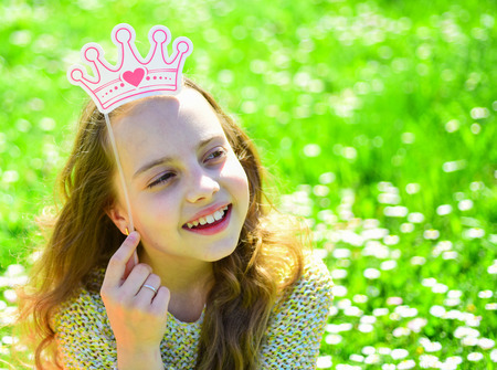 Girl on dreamy face spend leisure outdoors. Child posing with cardboard crown for photo session at meadow. Princess concept. Girl sits on grass at grassplot, green background.