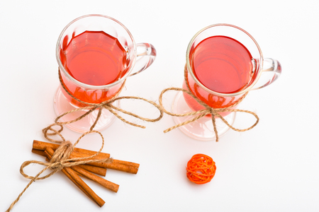 Mulled wine or hot beverage in glasses with decoration and cinnamon sticks. Glasses with mulled wine or hot drink tied with twine string on white background, close up. Hot drinks concept.