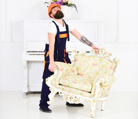 Delivery service concept. Courier delivers furniture in case of move out, relocation. Man with beard, worker in overalls and helmet lifts up armchair, white background. Loader carries armchair. Reklamní fotografie
