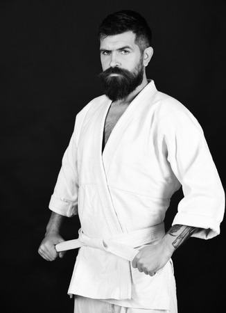 Karate man with serious and confident face in uniform. Man with beard in white kimono on black background.