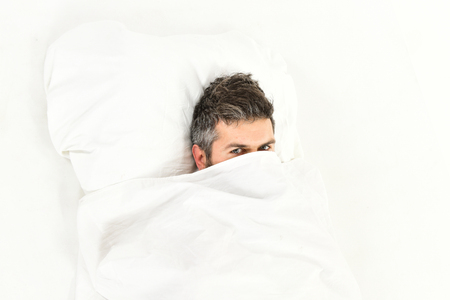 Guy hides face under blanket. Lazy and laziness Stock Photo