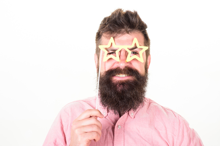 Hipster with beard and mustache on cheerful smiling face posing with star shaped glasses, copy space. Man holds party props star shaped eyeglasses, white background, close up. Superstar concept