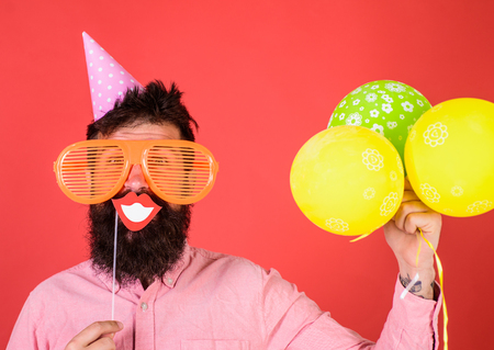 Hipster in giant sunglasses celebrating. Guy in party hat with air balloons celebrates. Photo booth fun concept. Man with beard on cheerful face holds smiling mouth on stick, red background