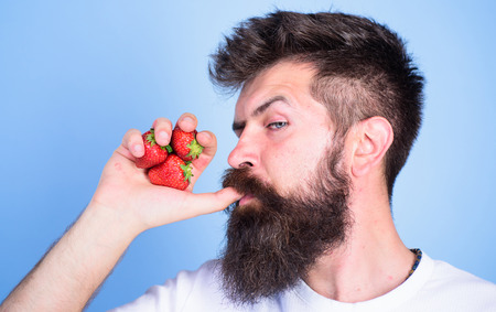 Man strict face enjoy fresh drink strawberry juice. Fresh juice concept. Man drinks strawberry juice suck thumb as drink straw blue background. Hipster bearded holds strawberries fist as juice bottle Stock Photo