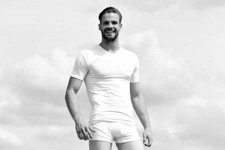 Gesundheits- und Fitnesskonzept. Macho trägt weißes T-Shirt und Unterwäsche. Männlicher Körper mit Torso, der weißes T-Shirt und Unterwäsche trägt