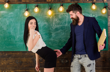 Schoolmaster punishes sexy student with slapping on her buttocks. Man with beard slapping sexy student, chalkboard on background.