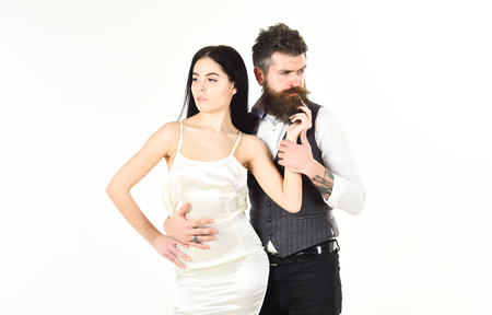 Wedding concept. Bearded hipster with bride dressed up for wedding ceremony, copy space. Woman in wedding dress and man in vest. Couple in love, bride and groom in elegant clothes, white background Reklamní fotografie