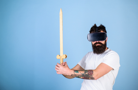 Gamer concept. Man with beard in VR glasses, light blue background. Hipster on serious face enjoy play game in virtual reality. Guy with head mounted display holds sword, play fighting game in VR. Stock Photo