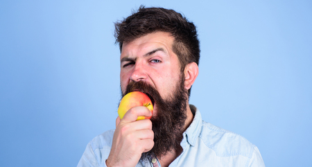 I love apples Man handsome hipster with long beard eating apple. Hipster hungry bites juicy ripe apple. Man diet nutrition eats fruit. Healthy nutrition concept. Fruit healthy snack always good idea. Banco de Imagens