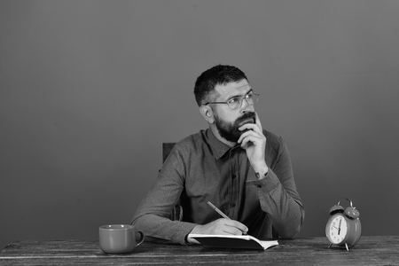 Cup, retro clock and red book on vintage table. Man with thinking face sits at wooden table. Man with beard and glasses writes in notebook on red background. Exam and studying concept.