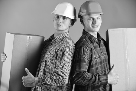 Siblings with cartons work as deliverymen. Delivery and parcel concept. Men with confident faces hold cardboard boxes on green background. Twin brothers in orange and white helmets show thumbs up. Stock Photo