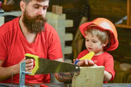 Educational games concept. Boy, child busy in protective helmet learning to use handsaw with dad. Father, parent with beard teaching little son to sawing while son play with toy saw. Stock Photo