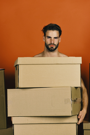 Delivery and moving in concept. Man with strong arms holding cardboard boxes. Macho with beard and serious face. Guy with pile of cartons isolated on red background.