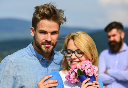 Couple in love dating while jealous bearded man watching wife cheating him with lover. Infidelity concept. Couple romantic date lovers bouquet flowers. Lovers hugs outdoor flirt romance relations. Stock Photo - 104376889