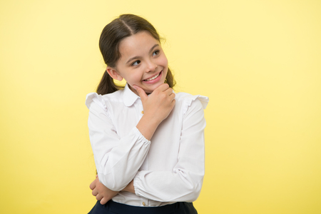 Happy child thinking on yellow background. Little daydreamer girl with cute smile. Lost in thoughts. Your dreams can send you far away. Adorable and smart, copy space