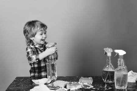 Cleaning activities concept. Kid with laughing face spraying water out of spray bottle. Child near table with cleaning supplies on. Boy in checkered shirt on blue background.