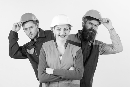 Team of architects, builders, labourers peeking behind leader isolated white background. Team and leadership concept. Woman, leader in hard hat with happy face stand in front of builders.